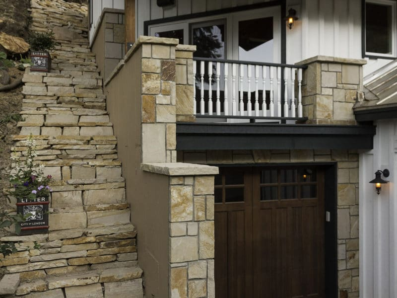 Exterior of a home with custom stone steps and small car port